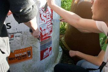 Menschen beim Entfernen von NPD-Plakaten